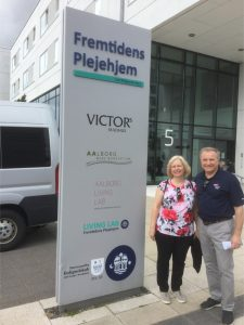 A man and woman stand next to a large sign with Danish writing.